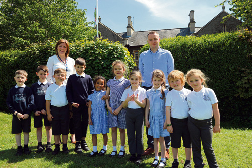 Head teacher Katherine Marks and deputy head Michael Backett with pupils outside the school